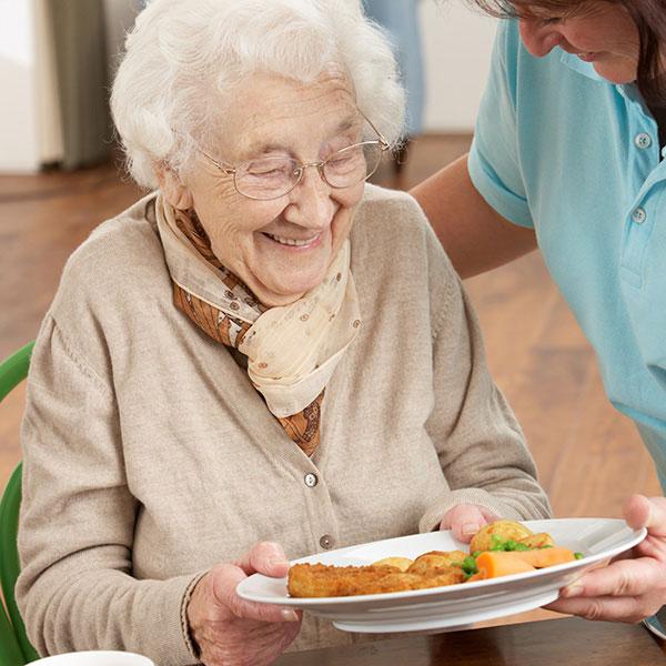 ältere Dame bekommt Menü serviert